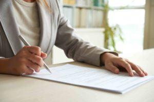 Frau unterzeichnet Erbverzichtsvertrag
