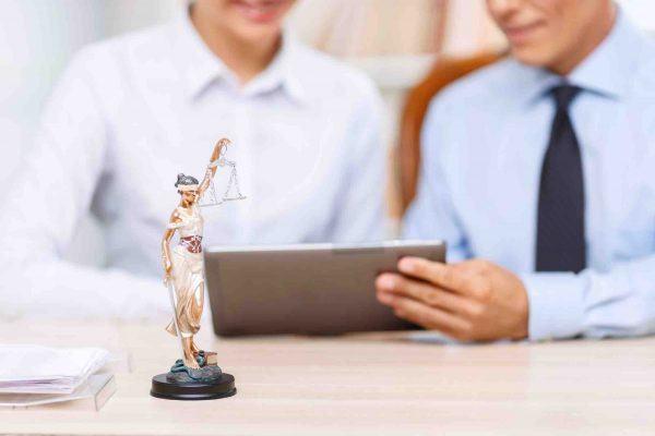 Anwalt zeig Klienten etwas am Laptop