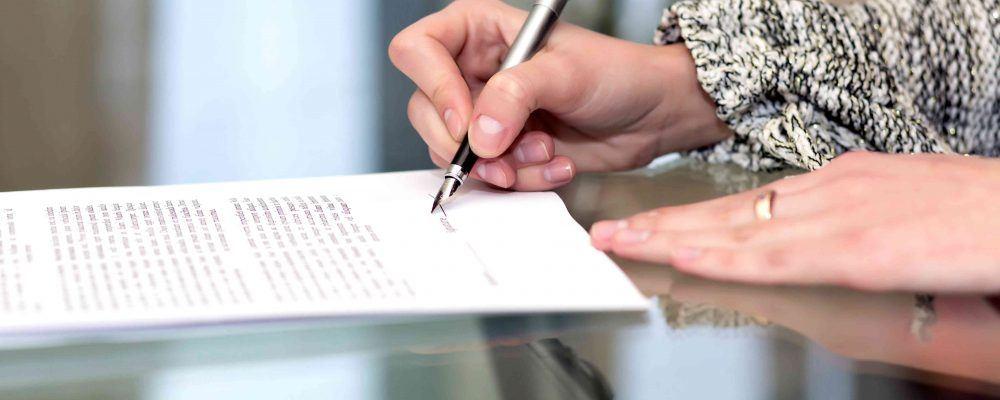 Frau unterzeichnet ein Erbausschlagung Formular