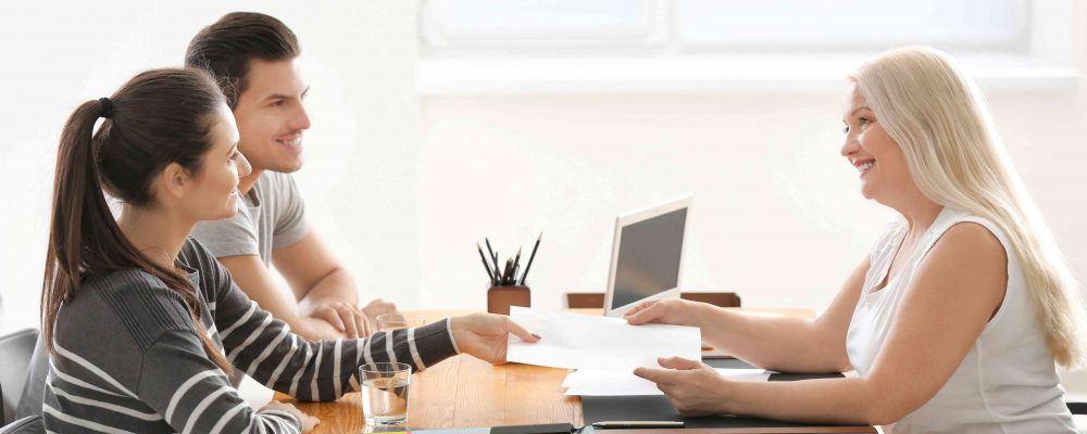 Junges Paar übergibt einer Anwältin einen Erbverzichtsvertrag
