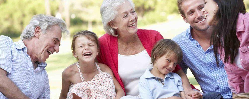 Familie sitzt im Grass und lacht