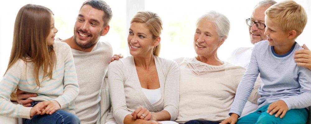 Familie sitzt auf Couch beisammen