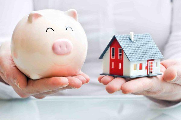 Sparschwein und Haus in der Hand