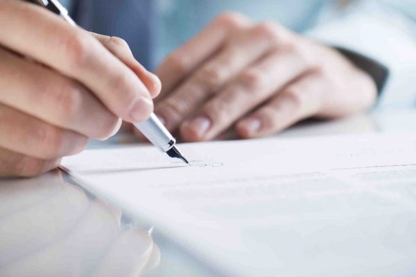 Mann unterzeichnet eine Erbverzichtserklärung