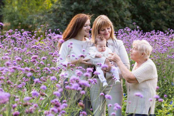 3 Generationen Grossmutter, Tochter und Kind stehen in der Blumenwiese