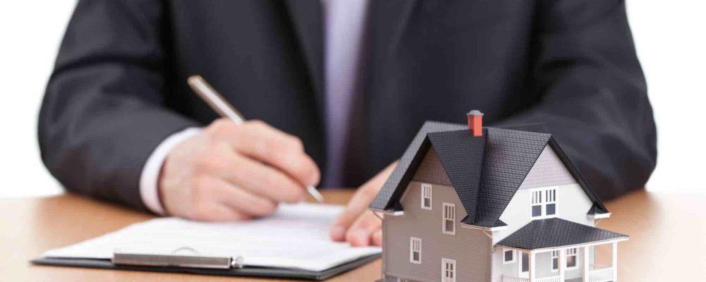Mann schreibt am Tisch mit einem kleinen Haus