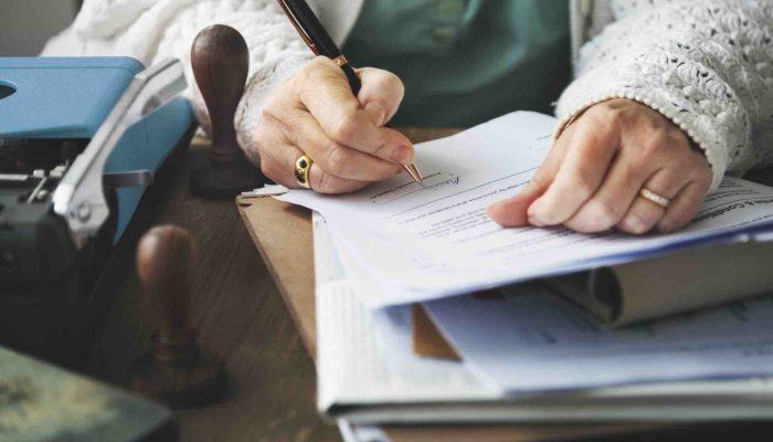 Alte Dame schreibt auf Papier