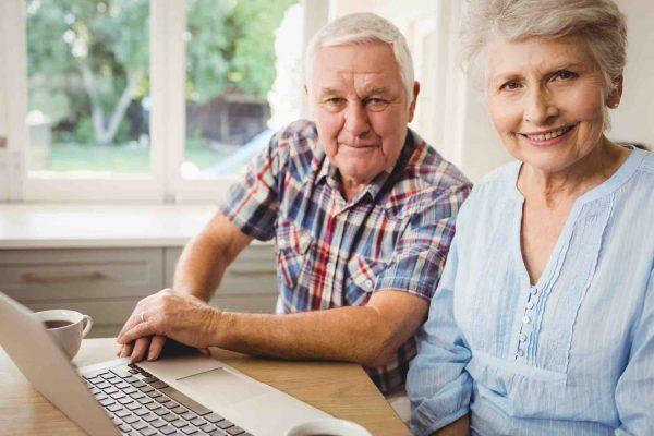 Älteres Ehepaar sitzt vor Laptop
